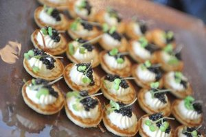 A close-up of appetizers served on a glass tray at a party.