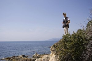 Marine biologist standing on cliff at beach