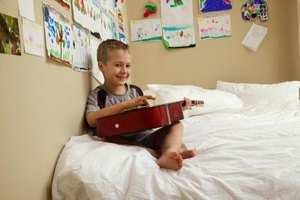 A boy playing the guitar in his bedroom with art on the walls.