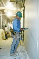A worker inserts screws into drywall in order to attach it to the existing framework.