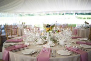 Wedding reception tables set up beneath a tent.
