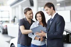 Couple reviewing purchase of a car paperwork with salesman.
