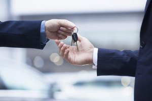 Salesman handing a client a set of new car keys.