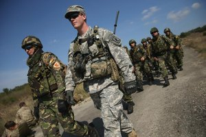 US army man walking with Romanian soldiers.