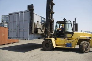 A man lifting a cargo trailer with a forklift in a shipping yard.