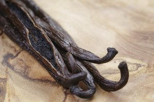 An open vanilla bean on olive wood.