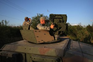 Two army soldiers looking out from top of tank