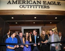 Celebrities cutting ribbon at American Eagle store