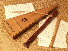 Renaissance instruments including a bowed psaltery, whistle and recorder on a cloth with sheet music.
