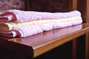 Towels folded on pullout wooden shelf.