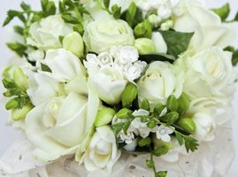 A close-up of a bridal bouquet made with white roses and orange blossoms.