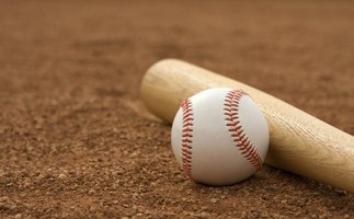 A baseball bat and ball lying on the field.