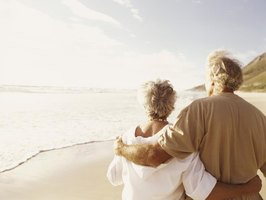 A retired couple walking along the beach.