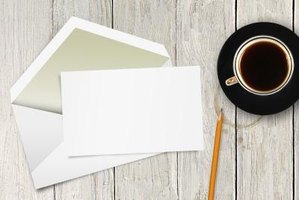 A blank card and envelope on a table next to a cup of coffee and a pencil.