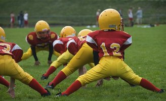 A youth football team stretching in a field of grass.