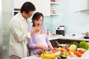 Pregnant woman chopping vegetables with her husband.