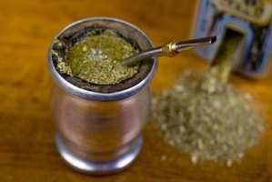 A mug of traditional yerba mate served with a metal straw.