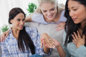 Woman showing friends her engagement ring at a bridal shower.