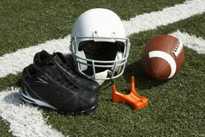 Helmet, shoes, tee and a striped football on the field.