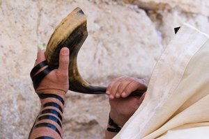 A Jewish man blowing a shofar at the Wailing Wall to celebrate Rosh Hashanah.