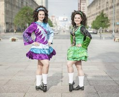 Two Irish dancers wearing wigs and in full costume outside.