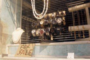 A close-up of items for sale in a pawn shop window.