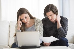 A young couple studies their debt in order to try and figure out the best way to get out of their financial mess