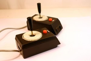 A pair of vintage video game joysticks on a table.