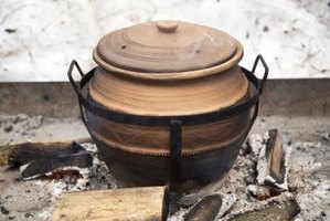 A ceramic clay pot on the fire.