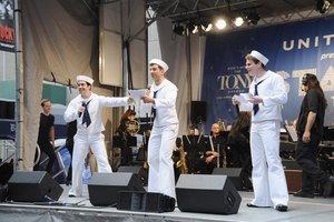 Three actors dressed as sailors performing on stage.