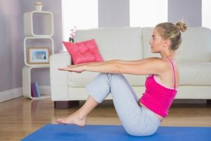 A woman doing pilates on a mat in her living room.