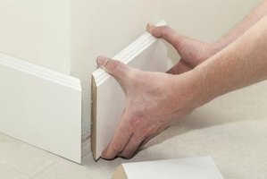 Man's hands installing white baseboards.