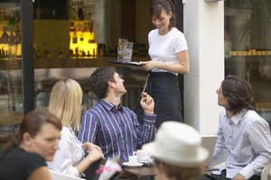 Waitress with tray talking to customer on outdoor patio.