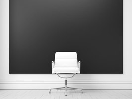 A wall painted with flat black paint highlights a white chair.
