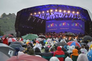 An orchestra performs onstage during the rain at an outdoor event.