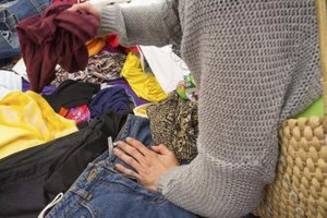 A close-up of a woman rummaging through used clothing.