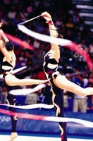 Rhythmic gymnasts create shapes in the air with their ribbons.