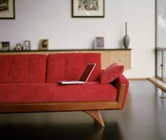 Whisper gray walls mute the insistent energy of a red sofa.