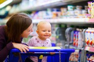 A woman affectionately talking to her baby while grocery shopping.