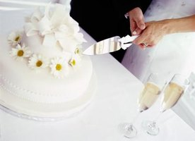 Close-up of couple cutting wedding cake.