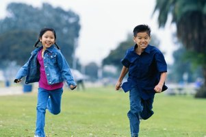 Two children running while playing outside.