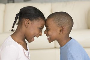 Young siblings pressing foreheads together and smiling.