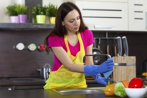A woman is  cleaning the kitchen.