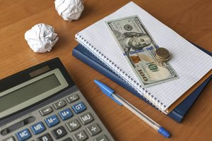 A stack of British pounds and a U.S. bank note on a desk with a calculator.