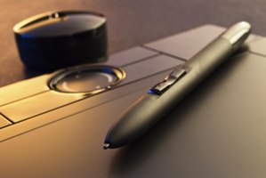 Close up of a graphic drawing tablet, stylus pen and pen holder.