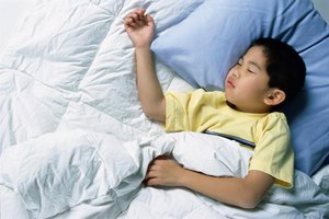 A boy sleeping on a feather top mattress.