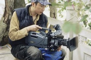 A videographer uses a professional camera in the field.