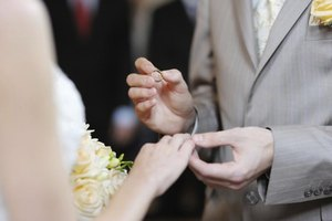 A groom placing a ring on the bride's finger during a wedding ceremony.
