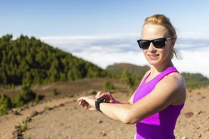 A runner adjusting her sportswatch on a natural trail.