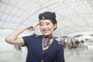 A flight attendant waving and winking in an airport.